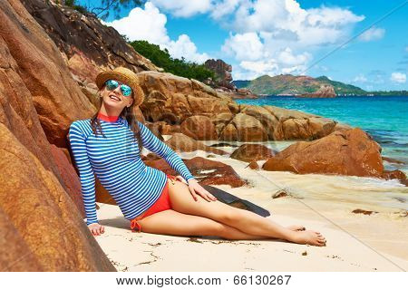 Woman at beautiful beach wearing rash guard. Seychelles, Curieuse island