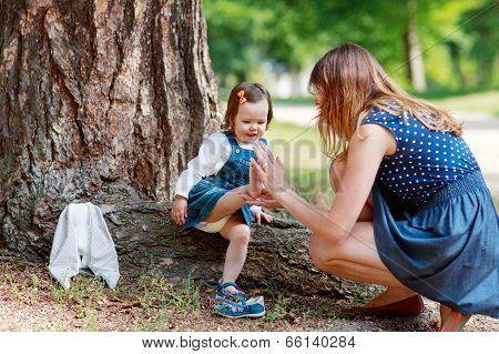 Happy Young Mother And Adorable Toddler Girl Walking Through Summer Park