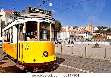 LISBON, PORTUGAL - MARCH 18: A typical tram 28 in Alfama district on March 18, 2014 in Lisbon, Portugal. The 28 line is one of the most used by tourists, because it connects Baixa and Alfama districts