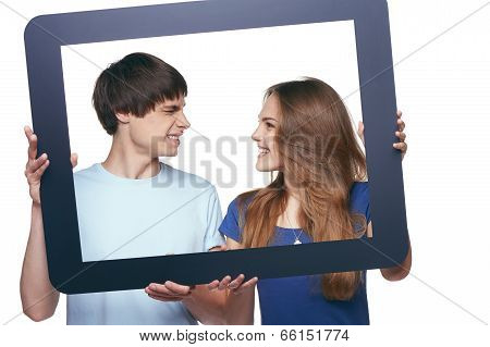Happy couple holding tablet frame and looking at each other