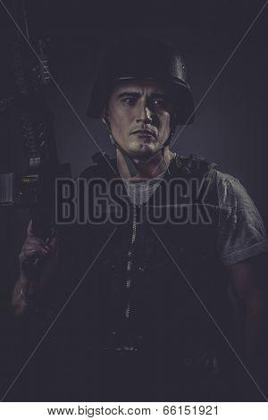gamer wearing protective helmet aiming pistol ,black armor and machine gun