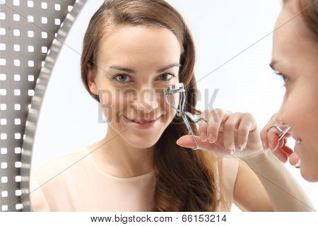 Woman curls lashes eyelash curler