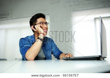 Happy asian man sitting at his workplace in office and talking on the phone