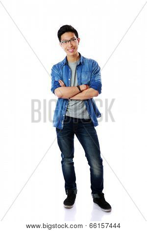 Full-length portrait of a happy asian man with arms folded over white background