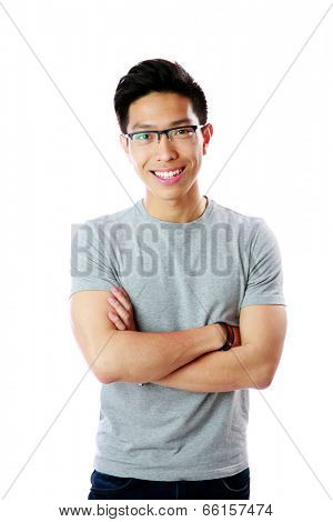 Portrait of a young happy asian man with arms folded over white background