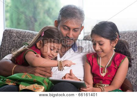 Indian family at home. Asian father and children using digital tablet computer, sitting on sofa, home schooling concept.
