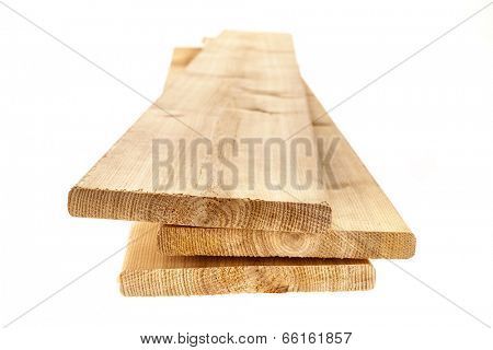 Three cedar one by six inch wood planks on white background