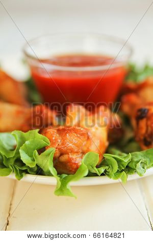 Chicken wings on salad with spicy tomato dip