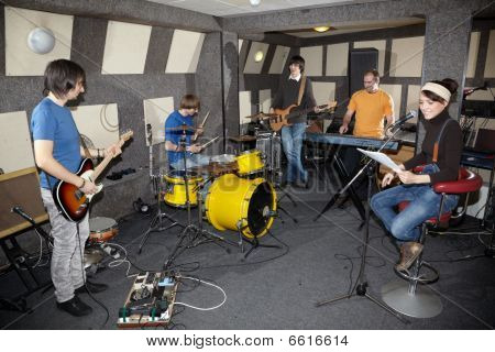 vocalist girl two musicians with electro guitars keyboarder and one drummer working in studio
