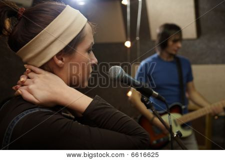 vocalist girl is singing. electro guitar player in out of focus