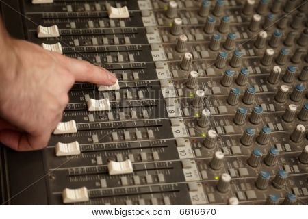 sound producer moving one fader of dusty sound mixer