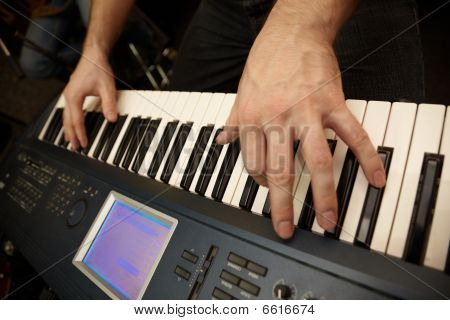 hands of keyboard player on keys of synthesizer.