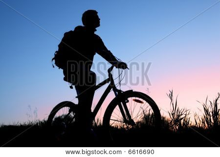 Silhouette Of The Bicyclist Against The Sunset Sky