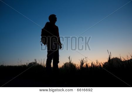 Silhouette Of The Man With A Backpack Against The Dark Sky