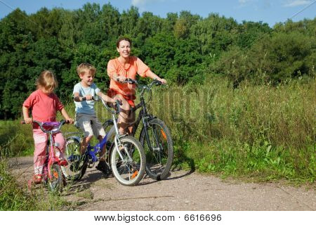 Mother With Son And Daughter Ride Bikes Outside The City