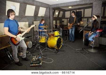 vocalist girl two musicians with electro guitars and one drummer is working in studio