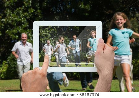 Hand holding tablet pc showing happy multi generation family racing towards camera