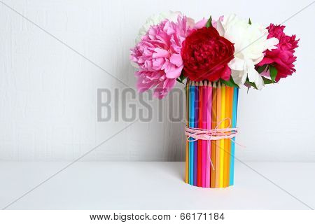 Beautiful flowers in colorful pencils vase in interior design