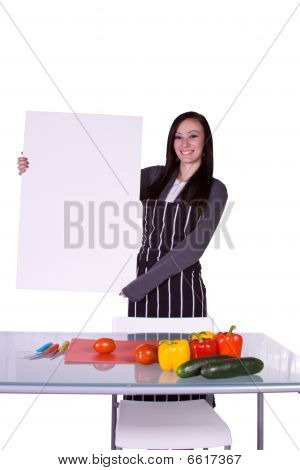 Beautiful Girl In The Kitchen Holding A Blank Sign