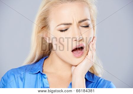 Attractive young blond woman with bad tooth ache holding her hand to her jaw with her mouth open as she frowns in pain