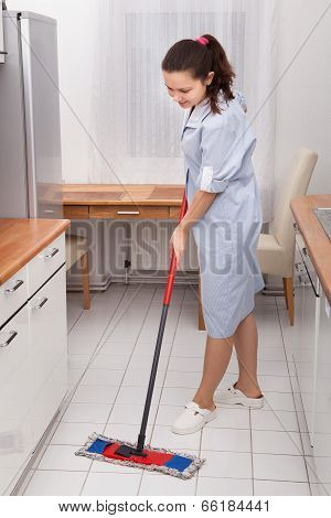 Young Maid Cleaning Kitchen Floor