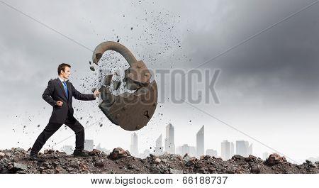 Businessman breaking stone lock with karate kick