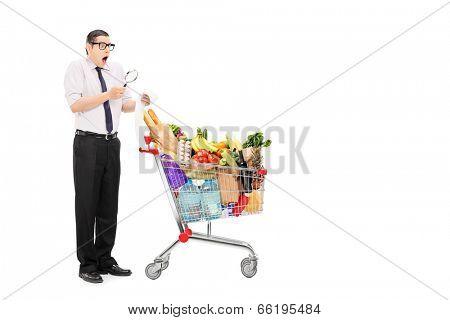Full length portrait of a shocked man examining the shopping bill