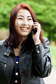 image of mongolian  - Mongolian girl talking on a phone outside - JPG