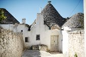 stock photo of conic  - Typical trulli houses with conical roof in unesco world heritage Alberobello Apulia southern Italy - JPG