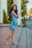 picture of hail  - Beautiful brunette girl in a hat held out her hand and hailing - JPG