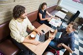 stock photo of angles  - High angle view of male and female customers spending leisure time in cafeteria - JPG