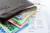 stock photo of statements  - Old leather wallet and money in various banknote and coin on credit card or financial statement - JPG