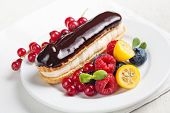 foto of eclairs  - Chocolate eclair with berries on white plate - JPG