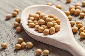 stock photo of soya beans  - Soya beans on a wooden spoon on a wooden table - JPG