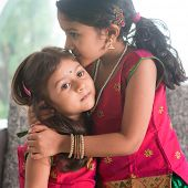 stock photo of sari  - Indian girl kissing her younger sister with love - JPG