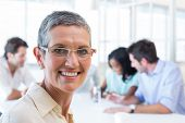 picture of half-dressed  - Attractive businesswoman smiling at the camera during a business meeting - JPG