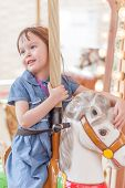 stock photo of carousel horse  - Young girl riding carousel horse at amusement park - JPG
