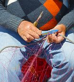 image of fishnet  - Fisherman is repairing the fishnet. Close up hands ** Note: Soft Focus at 100%, best at smaller sizes - JPG