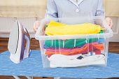 stock photo of maids  - Maid Holding Laundry Basket Kept On Ironing Board - JPG
