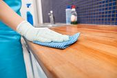 stock photo of housekeeper  - Closeup Of Young Woman Wearing Apron Cleaning Kitchen Worktop - JPG