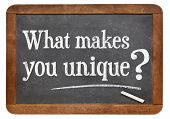 stock photo of uniqueness  - What makes you unique question  on a vintage blackboard isolated on white - JPG