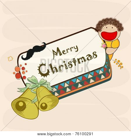 Cute little boy holding board or poster decorated with jingle bell and moustache for Merry Christmas celebrations.