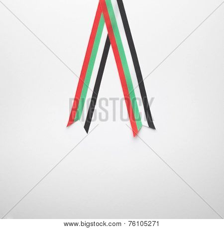 A piece of striped ribbon in the colours of the UAE flag.