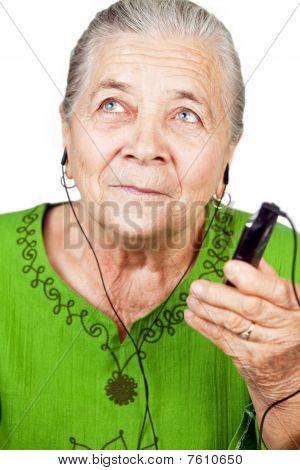 Senior Woman Listening Music At Mobile Phone