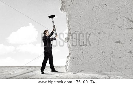 Young determined businessman crashing wall with hammer