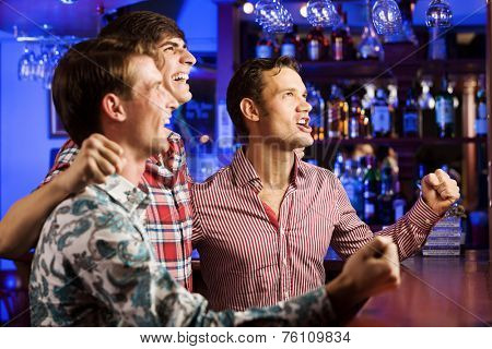 Three young men at bar watching match and shouting