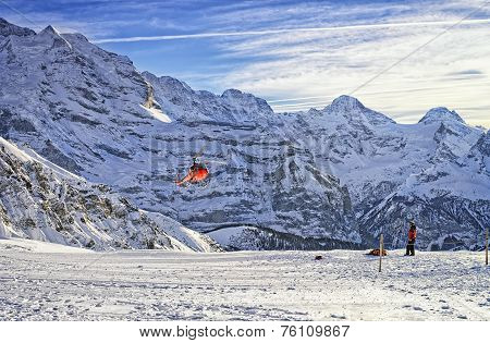 Red Helicopter Flying Over Swiss Ski Resort Near Jungfrau Mountain