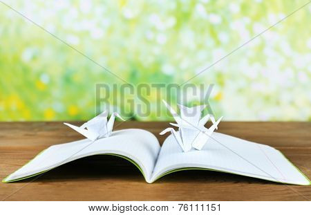 Origami cranes on notebook on wooden table, outdoors