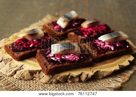 Canape herring with beets on rye toasts, on wooden board, on wooden table background