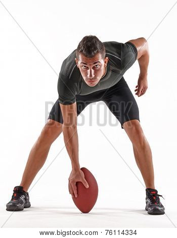 Rugby player holding a ball on white background.Strong player portrait.